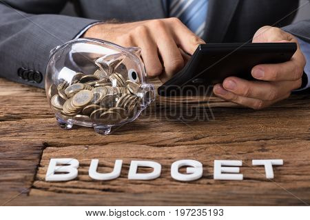 Closeup of businessman using calculator by piggybank with budget text on table