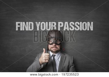 Portrait of businessman wearing aviator helmet and glasses showing thumbs up under find your passion text on blackboard