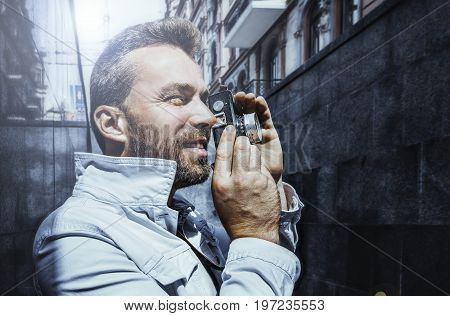 Man with beard taking picture on old film camera, city view background
