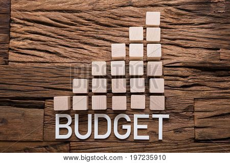 Closeup of budget text by increasing bar graph blocks on wooden table