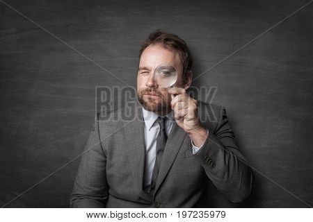 Portrait of businessman looking through magnifying glass against blackboard