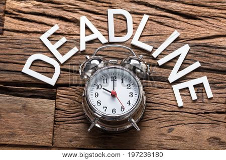 High angle view of deadline text by alarm clock on wooden table