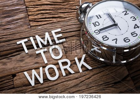 High angle view of time to work text by alarm clock on wooden table