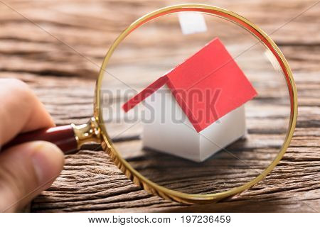 Cropped image of businessman examining model home with magnifying glass on wooden table