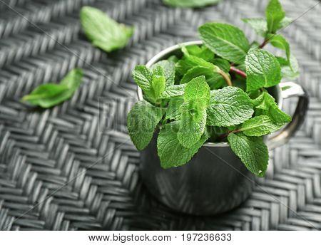 Mug with fresh lemon balm leaves on table