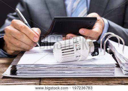 Midsection of businessman calculating invoice with thermostat radiator on documents at table