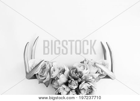 Silver deer antlers decorated with flowers. Copy space.