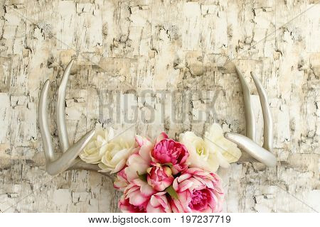 Silver deer antlers decorated with flowers against birch bark. Copy space