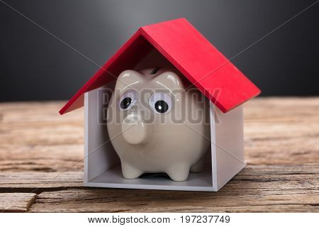 Closeup of piggybank in model home on wooden table against black background