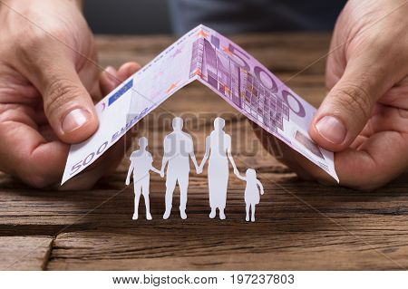 Hands covering paper family under house roof made from 500 euro papernote on wooden table