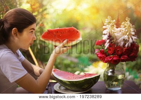 teenager girl eat water melon with rose bouquet in vase close up photo on green sumer garden background