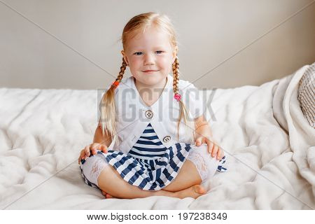 Portrait of cute adorable white Caucasian smiling preschool girl sitting on bed looking in camera. Child girl with light fair hair with plaits blue eyes wearing striped dress.