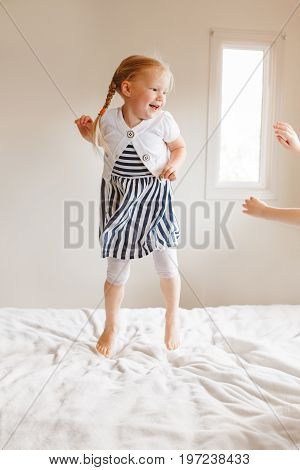 Portrait of cute finny white Caucasian blonde girl jumping on bed at home and playing with sibling friend. Hilarious active kid having fun indoors. Authentic lifestyle childhood concept. poster