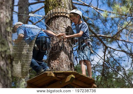 MEZIO, PORTUGAL - JULY 22, 2017: young adventurous kid prepares to a slide in zip lining thru the forest. July 22, 2017, Mezio, Portugal.