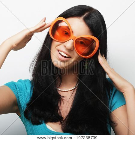 Party image. Playful young woman with big party glasses and crown. Ready for good time.