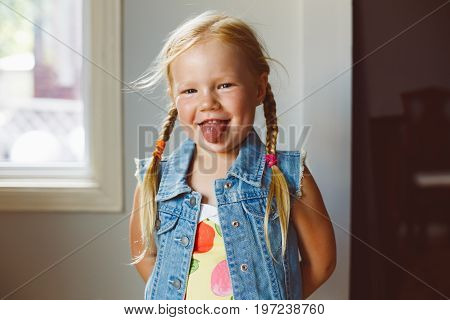 Closeup portrait of cute adorable funny white blonde Caucasian preschool girl looking in camera showing tongue. Child girl with light fair hair with plaits smiling having fun.