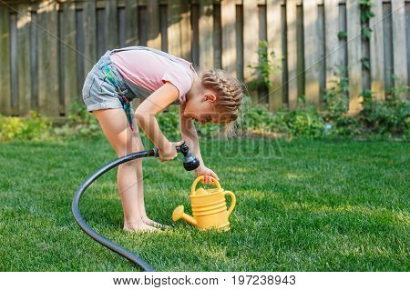 Portrait of little girl filling watering pot from gardening house on backyard on summer day. Child with watering can in garden. Lifestyle family activity. Kids responsibility for doing home chores.