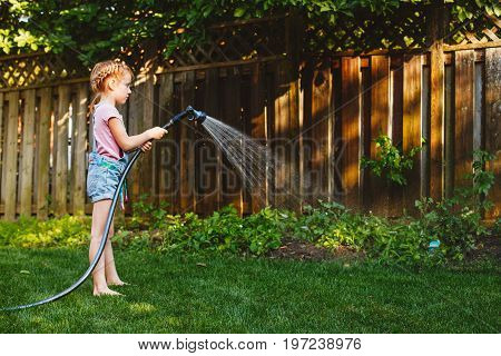 Portrait of girl watering plants vegetables with gardening house on backyard on summer day. Child playing with water outside. Lifestyle family activity. Kids responsibility for doing home chores.