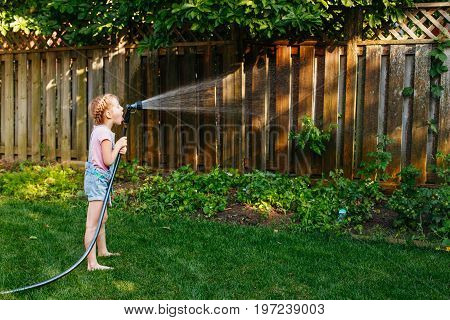 Portrait of girl watering plants vegetables with gardening house on backyard on summer day. Child playing drinking water outside. Lifestyle family activity. Kids responsibility for doing home chores.