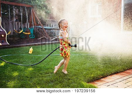 One girl splashing with gardening house on backyard on summer day. Child playing with water outside at sunset. Candid moment lifestyle home kid activity.