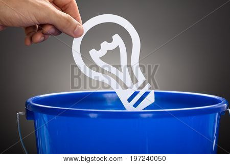 Cropped hand of businessman throwing paper light bulb in blue bucket against gray background