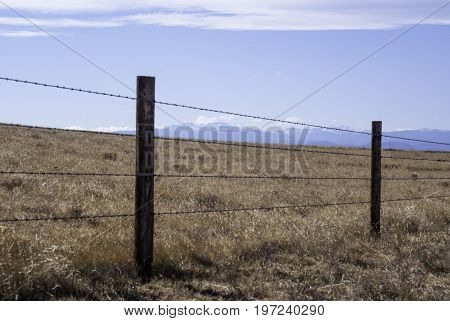 Barbed wire fence to contain livestock on the high plains of Wyoming USA with the Rocky Mountains in the background.