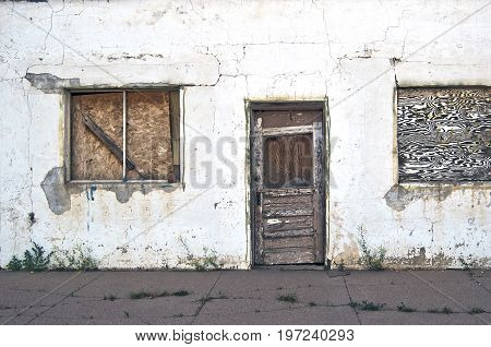 Run-down building abandoned and forgotten with boarded up door and windows