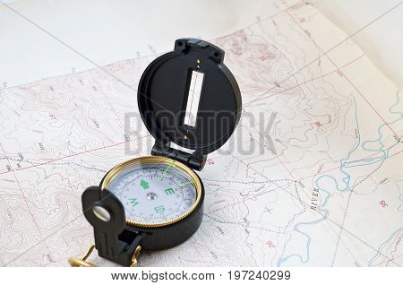 Compass sitting on a spread out topographical map
