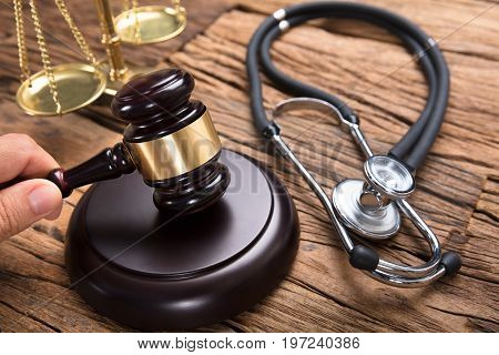 Judge hitting mallet by stethoscope and justice scale on wooden table in courtroom