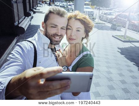 Smiling man and woman taking picture of themselves on cellphone, background of street. Happy married wife and husband during vacantion