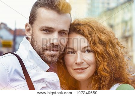 Middle aged married man and woman posing on camera. Red haired woman and bearded man, street sunshine background