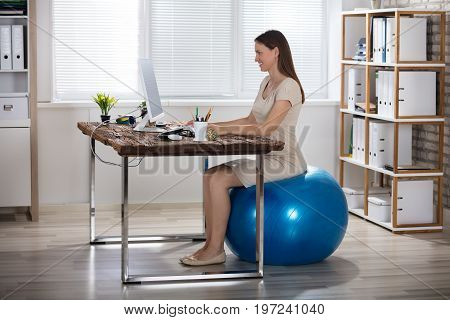 Smiling Young Businesswoman Sitting On Fitness Ball Using Computer