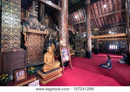 LUANG PRABANG LAOS - MARCH 11 2017: People praying inside Wat Xieng Thong Buddhist temple located in the city Luang Prabang Laos