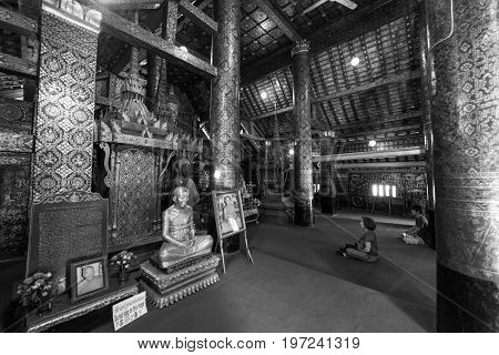 LUANG PRABANG LAOS - MARCH 11 2017: Black and white picture of people praying inside Wat Xieng Thong Buddhist temple located in the city Luang Prabang Laos
