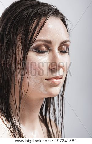 Beauty Concepts and Ideas. Portrait of Caucasian Brunette Girl with Closed Eyes Showing Wet and Shining Skin and Wet Hair. Creative Makeup. against Grey. Vertical Image