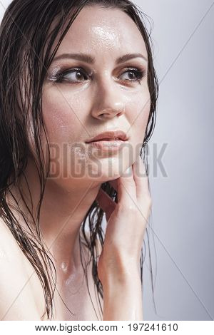 Beauty Concepts and Ideas. Portrait of Caucasian Sensual Brunette Touching Neck and Showing Wet and Shining Skin and Wet Hair. Creative Makeup. Against Grey. Vertical Image Orientation