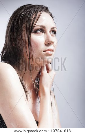 Beauty Concepts and Ideas. Closeup Portrait of Caucasian Sensual Brunette Touching Neck and Showing Wet and Shining Skin and Wet Hair. Creative Makeup. Against Grey. Vertical Image