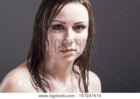 Beauty Concepts and Ideas. Closeup Portrait of Caucasian Sensual Brunette Showing Wet and Shining Skin and Wet Hair. Against Dark Grey Background. Horizontal Image Orientation
