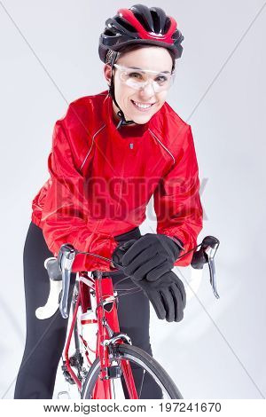 Cycling Ideas And Concepts. Portrait of Caucasian Female Cyclist Equipped in Cycling Outfit and Posing With Road Bike In Studio.Vertical Image