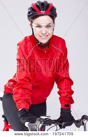 Cycling Concepts. Portrait of Caucasian Female Cyclist Equipped in Cycling Outfit and Posing With Road Bike In Studio. Vertical Composition