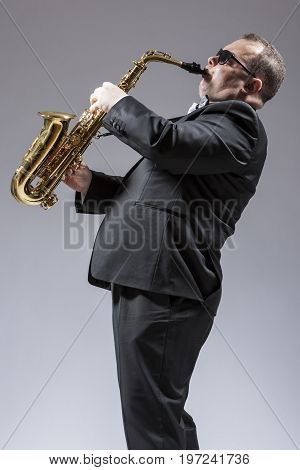 Music Concepts. Portrait of Mature Caucasian Saxophone Player in Sunglasses Playing the Saxophone in Studio Environment. Vertical Shot
