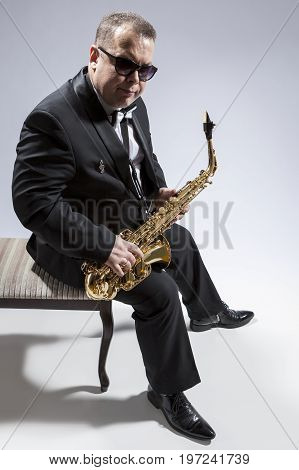 Portrait of Mature Relaxed Caucasian Saxophone Player in Sunglasses Posing with Saxophone While Sitting on Chair in Studio Environment. Vertical Image