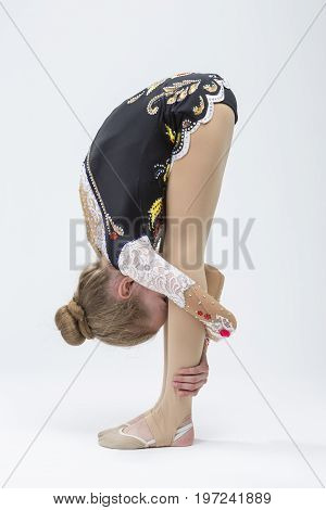 Caucasian Female Rhythmic Gymnast Athlete In Professional Competitive Suit Doing Backbend Stretching Exercise While Posing in Studio Against White. Vertical Composition