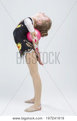 Young Caucasian Female Rhythmic Gymnast Athlete In Professional Competitive Suit Doing Backbend Stretching Exercise With Medium Ball in Studio Against White. Vertical Shot