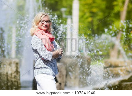 Portrait of Mature Middle Aged smiling Blond Woman Wearing Spectacles Posing Outdoors in Park.Hands Folded in Front. Horizontal Shot