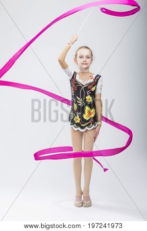 Sport Concepts. Little Caucasian Female Rhythmic Gymnast In Professional Competitive Suit Doing Artistic Ribbon Spirals Exercises in Studio On White. Vertical Image