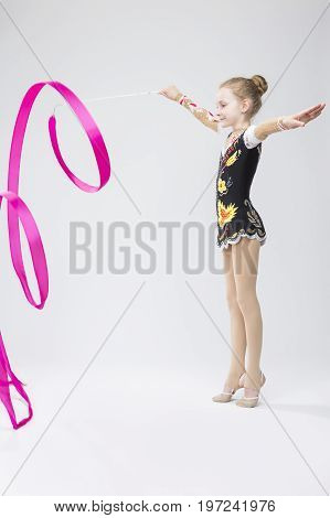 Professional Sport Concepts. Little Caucasian Female Rhythmic Gymnast In Professional Competitive Suit Doing Artistic Ribbon Spirals Exercises in Studio Against White. Vertical Shot