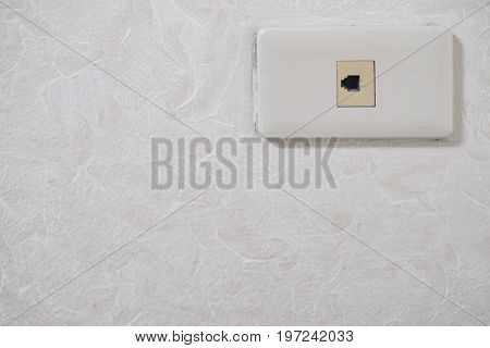 Old socket for internet cable telephone port wall socket on white wall.