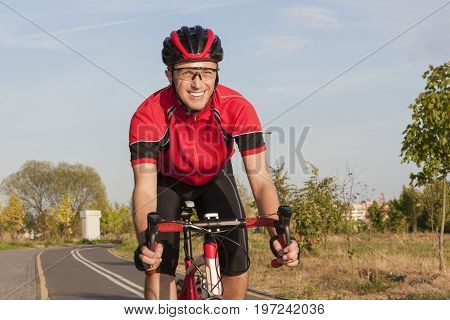 Cycling Concepts and Ideas. Smiling Caucasian Road Cyclist During Ride on Bike Outdoors. Completely Equipped in Professional Outfit.Horizontal Image Orientation