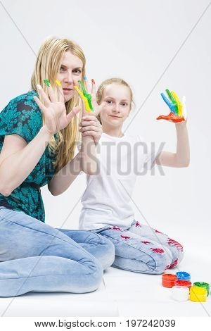 Family Activity Concepts. Mother with Little Daughter Making a Hand Pint Together Indoors.Showing Palms With Messy Paint. Against White. Vertical Image Composition
